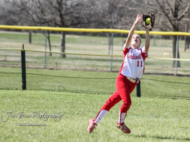 Hoisington Lady Cardinal Keeley Wolf (#11) catches a fly ball in the top of the first inning. The Hoisington Lady Cardinals defeated the Halstead Lady Dragons by a score of 12 to 2 in six innings at Logan Field in Hoisington, Kansas on April 27, 2018. (Photo: Joey Bahr, www.joeybahr.com)