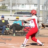 Hoisington Lady Cardinal Brooke Steinert (#15) starts to swing at a pitch in the top of the fifth inning. The Hoisington Lady Cardinals defeated the Halstead Lady Dragons by a score of 12 to 2 in six innings at Logan Field in Hoisington, Kansas on April 27, 2018. (Photo: Joey Bahr, www.joeybahr.com)