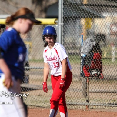 Hoisington Lady Cardinal Trinity Dolezal (#33) watches the pitcher to see when she can get a lead from first base in the bottom of the sixth inning. The Hoisington Lady Cardinals defeated the Halstead Lady Dragons by a score of 12 to 2 in six innings at Logan Field in Hoisington, Kansas on April 27, 2018. (Photo: Joey Bahr, www.joeybahr.com)