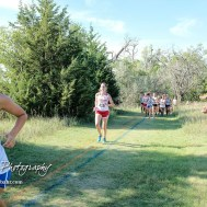 Katie Bahr (#419) of McPherson pursues Jacqeline Lewton (#374) of Hutchison. The Great Bend Cross Country Invitational was held at Lake Barton near Great Bend, Kansas on August 30, 2018. (Photo: Joey Bahr, www.joeybahr.com)