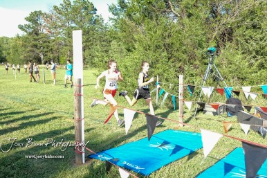 Eleanor Been (#497) takes thirtieth place in front of McPherson's Hannah Dossett (#422). The Great Bend Cross Country Invitational was held at Lake Barton near Great Bend, Kansas on August 30, 2018. (Photo: Joey Bahr, www.joeybahr.com)