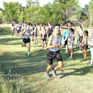 Noe Rodriguez-Jimenez (#170) of Garden City braces for the impending impact of water tossed his way by a spectator. The Great Bend Cross Country Invitational was held at Lake Barton near Great Bend, Kansas on August 30, 2018. (Photo: Joey Bahr, www.joeybahr.com)