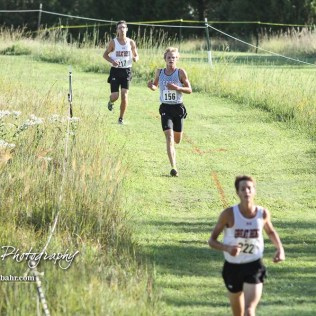 Great Bend's Sage Cauley (#217) pursues Garden City's Ethan Fisher (#156) down an incline in the course. The Great Bend Cross Country Invitational was held at Lake Barton near Great Bend, Kansas on August 30, 2018. (Photo: Joey Bahr, www.joeybahr.com)