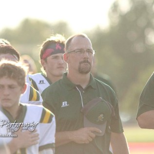 Pratt Greenback Head Coach Jamie Cruce salutes the flag during the national anthem. The Pratt Greenbacks defeated the Hoisington Cardinals by a score of 34 to 0 at Elton Brown Field in Hoisington, Kansas on August 31, 2018. (Photo: Joey Bahr, www.joeybahr.com)