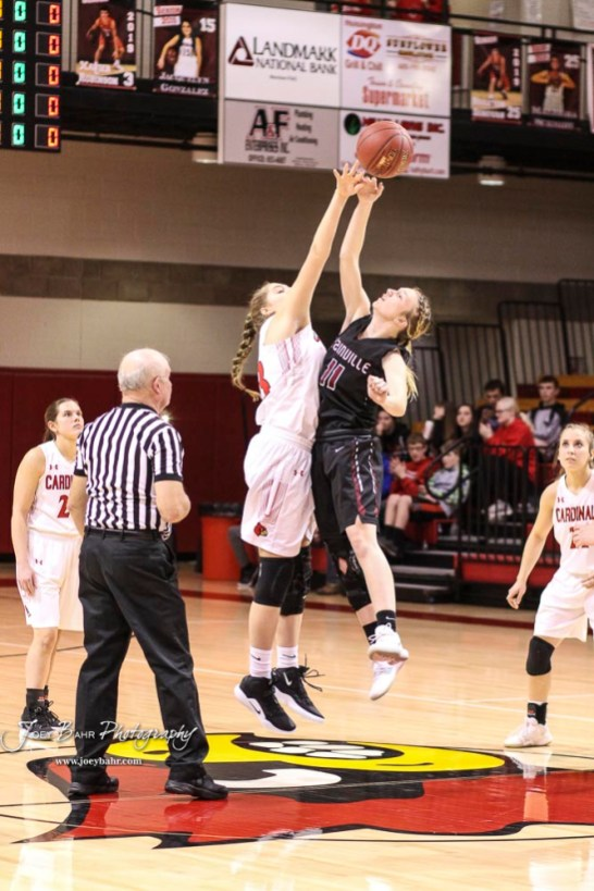 Hoisington Lady Cardinal #43 Brielle Romeiser and Plainville Lady Cardinal #11 Kate McClellan jump for the ball during the opening tip off. The Plainville Lady Cardinals defeated the Hoisington Lady Cardinals by a score of 49 to 35 at the Hoisington Activity Center in Hoisington, Kansas on February 5, 2019. (Photo: Joey Bahr, www.joeybahr.com)