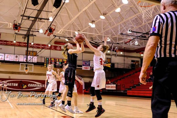 Hoisington Lady Cardinal #32 Kelsi Dalton touches the ball as Plainville Lady Cardinal #11 Kate McClellan shoots resulting in an alternate possession in the second quarter. The Plainville Lady Cardinals defeated the Hoisington Lady Cardinals by a score of 49 to 35 at the Hoisington Activity Center in Hoisington, Kansas on February 5, 2019. (Photo: Joey Bahr, www.joeybahr.com)