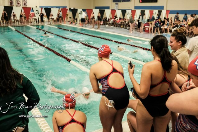 Teammates cheer on a fellow Dodge City swimmer during the 200 yard Medley Relay. The Great Bend Girls Swimming Invitational was held at the Kirkman Activity Center on the campus of Barton Community College in Great Bend on 4 20190426, 2019. (Photo: Joey Bahr, www.joeybahr.com)