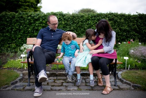 Family of four sitting on a bench at the botanic gardens