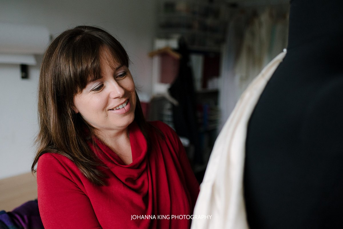 Sarah Foy's smiling while working on a wedding dress prototype