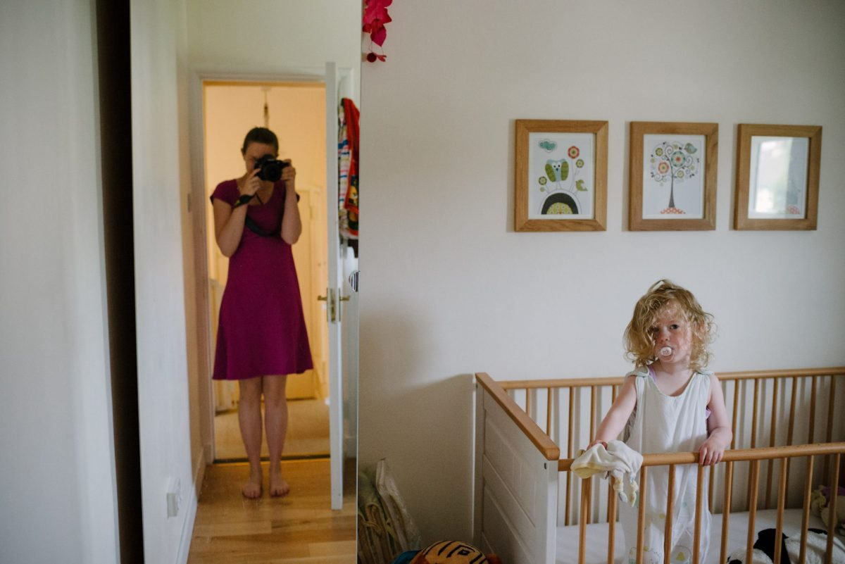 A mirror selfie of a mum coming in the bedroom to pick up her daughter after her nap. 2nd of 8 Ways for mums to exist in family photos