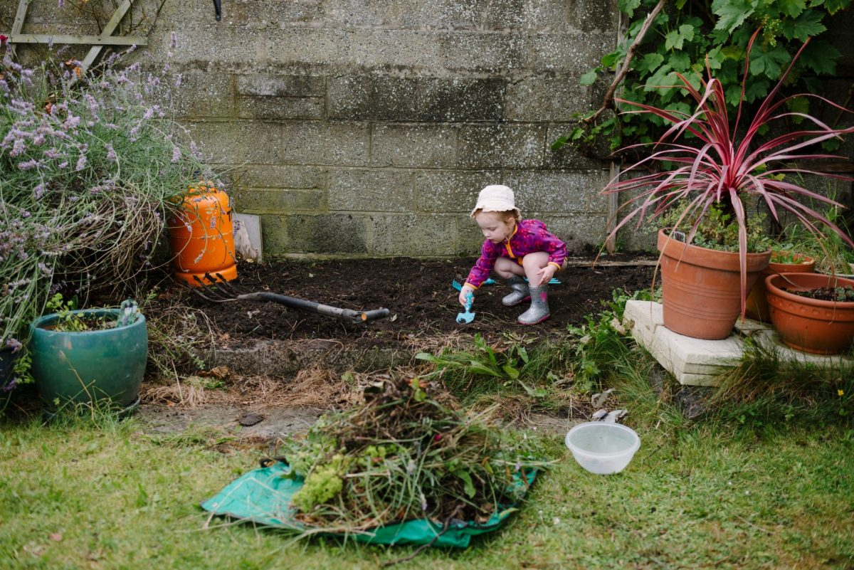 Little girl gardening in wellies and bare legs