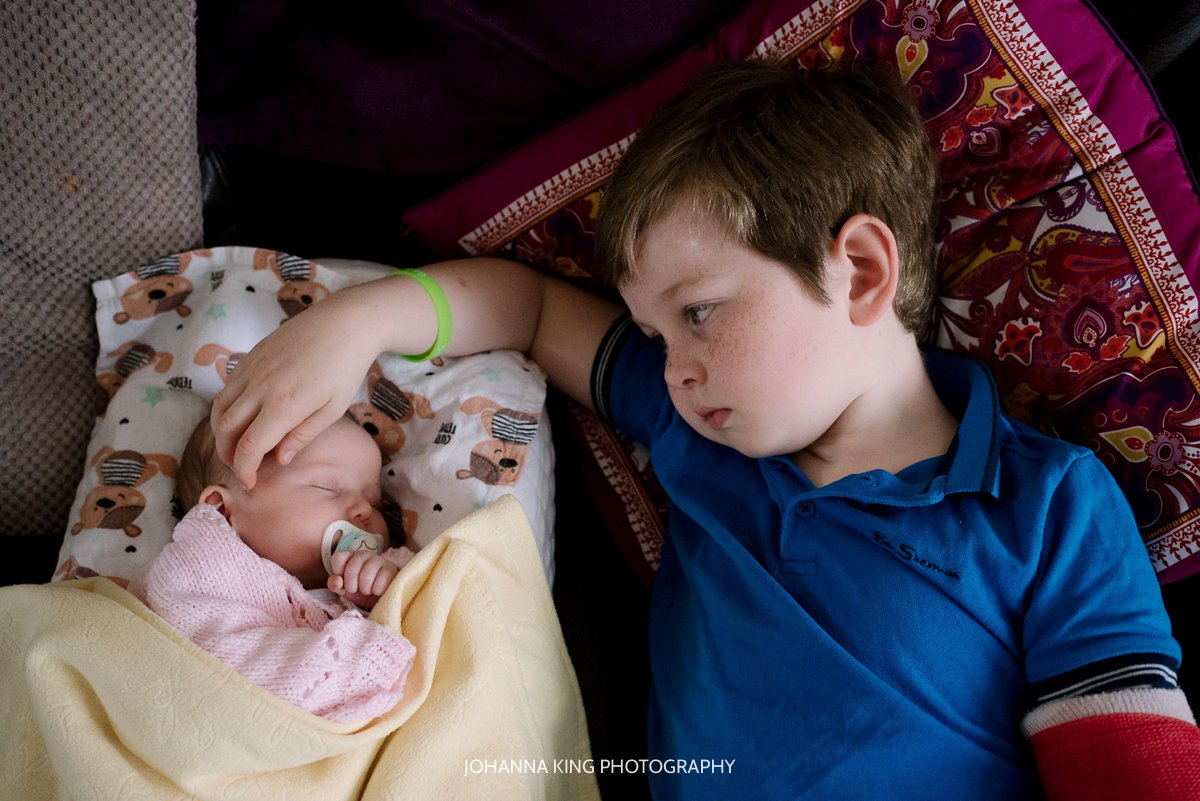 Big brother stroking his newborn sister's head to calm her down