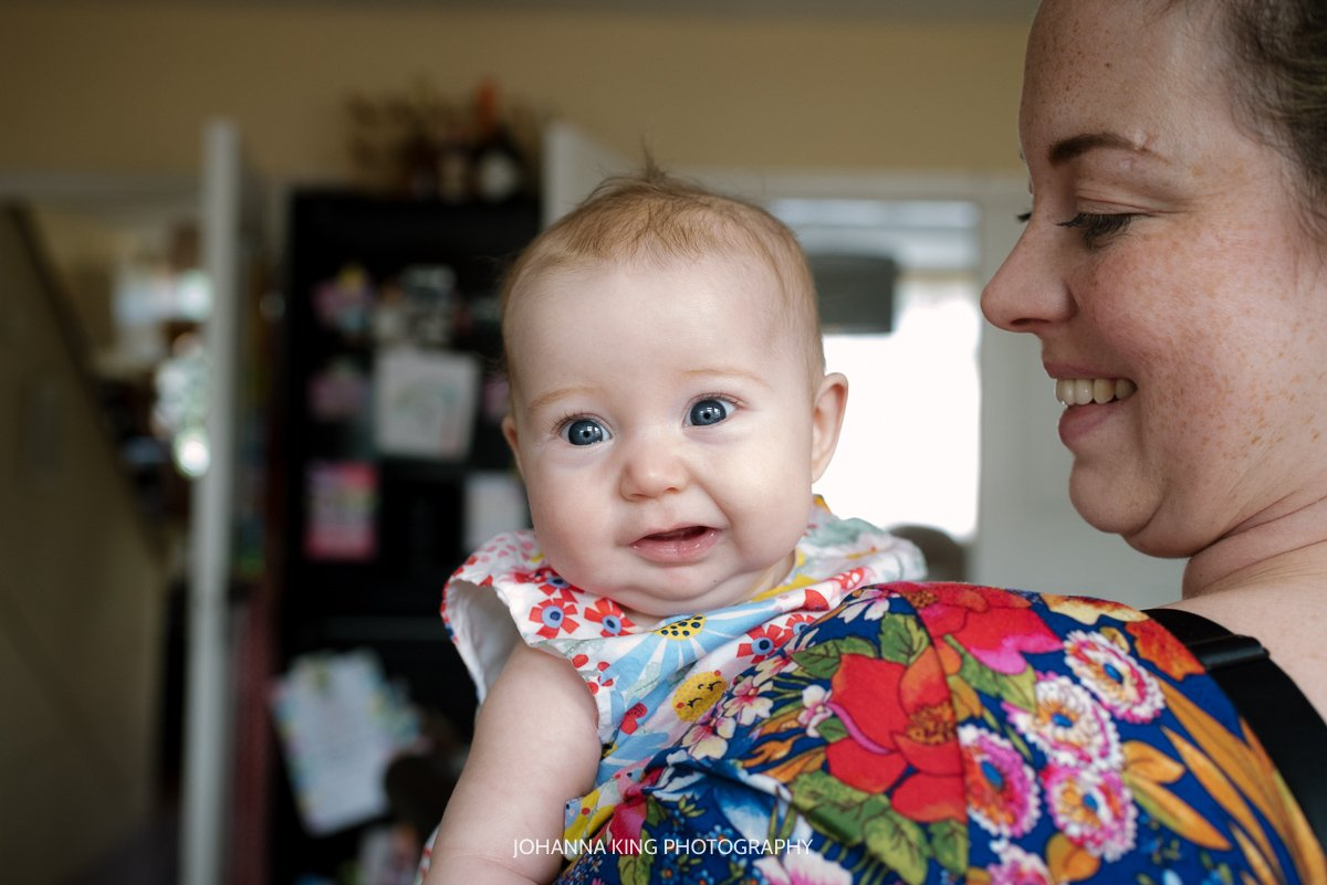 Baby girl with big blue eyes smiling at the camera