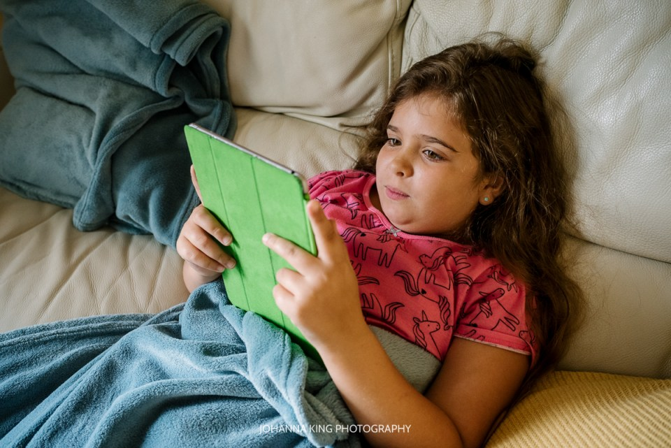 A girl, daughter, reading a book on her tablet on her family vacation