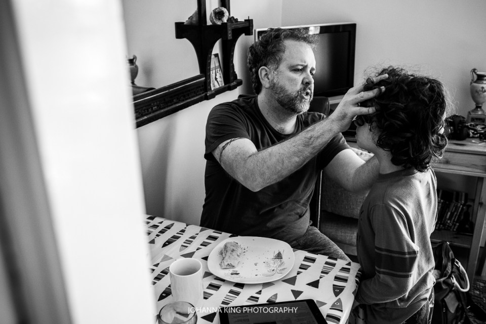 A father checking his son's face for chocolate