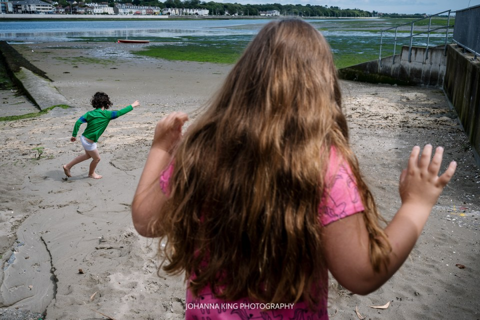 Siblings walking to the beach with funny body language.