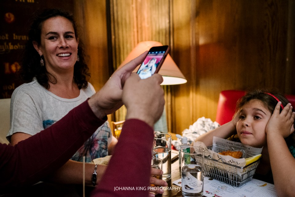 A father takes a photo on his phone of his daughter in front of her meal in Dublin