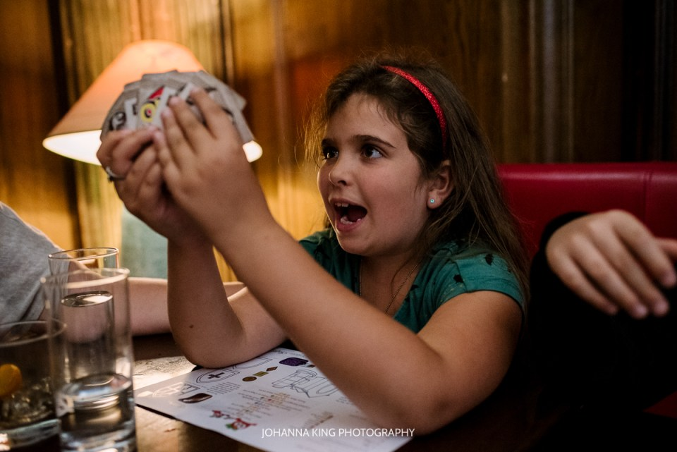 Funny expression of daughter looking at her cards of UNO