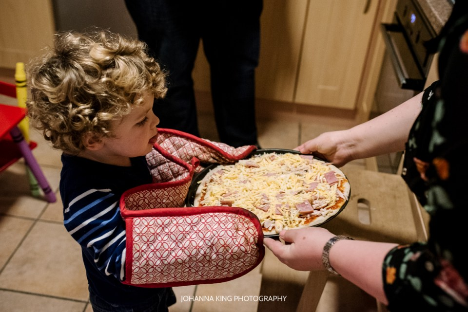 Little boy sticking his tongue out while taking the pizza with the oven gloves