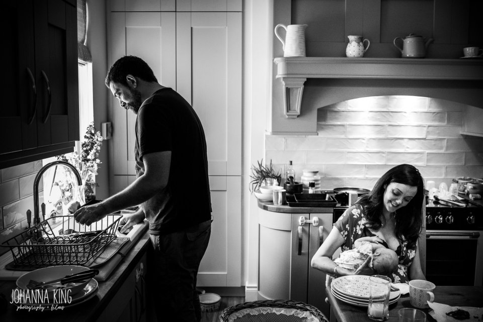 Father rinsing the dishes while the mother is breastfeeding her baby daughter at the kitchen table - Documentary Newborn Photography Example