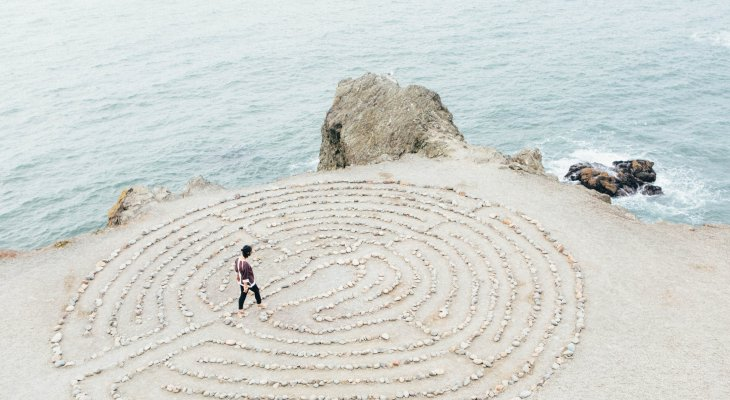 Woman walking a labyrinth by the sea