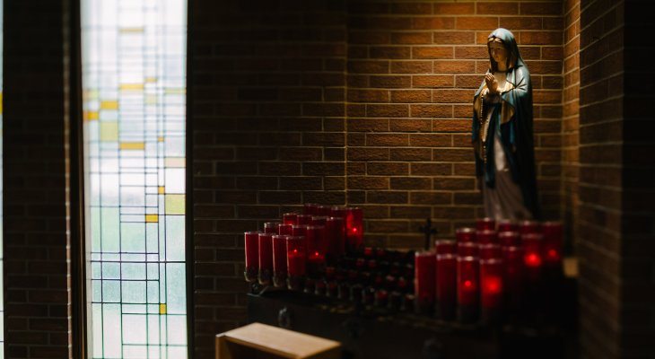 Votive candles and statue of St Mary
