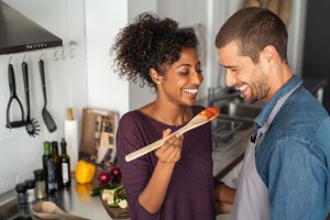 Man and woman in a kitchen. Woman holding a spoon with food