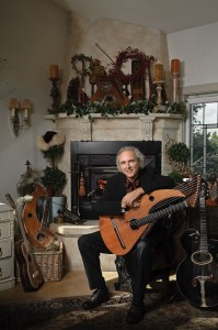 John Doan Victorian Christmas Concert with harp guitar in front of fire place.