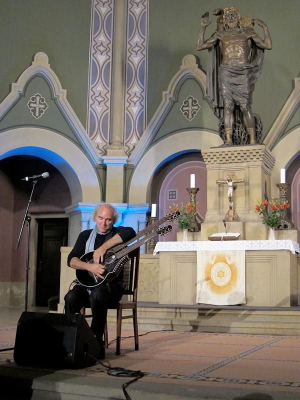 John Doan in Concert playing harp guitar in ancient church