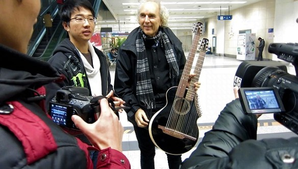 John Doan and his harp guitar greeted in Xi'an China by reporters
