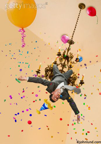 Office Party Craziness Gone Too Far A Businessman Swings From Chandelier And Holds Noise Maker Amid The Balloons Confetti
