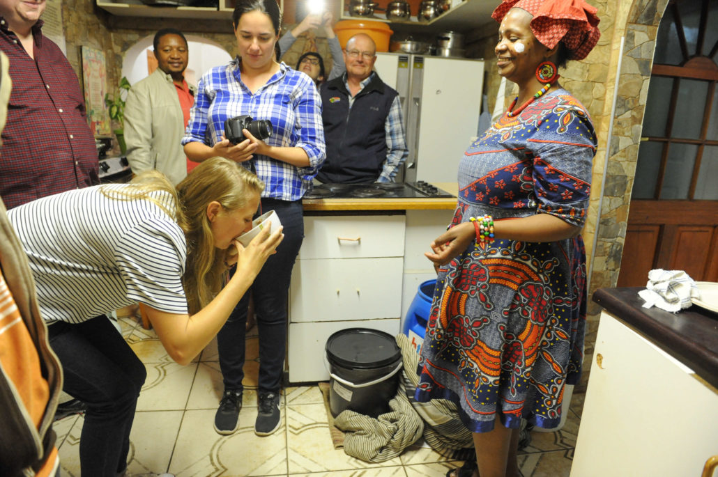Our host, Nocawe, invites us into her mother's kitchen where they are in the process of brewing beer. The tradition is to bow to the gods while taking a sip. One of the writers in our group obliges.