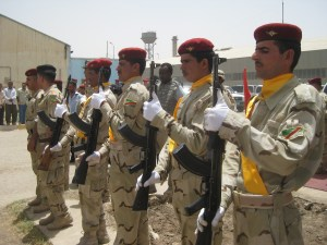 An honor guard from the 3rd Battalion, 41st Iraqi Army brigade presents arms at a ceremony for Iraq's National Sovereignty Day, June 30, at a defunct sugar factory near Majaar Al Kabir in Maysan province. Iraqi soldiers occupied the base vacated by Soldiers from Company B, 4th Battalion, 6th Infantry Regiment attached to 2nd Squadron, 13th Cavalry Regiment following the ceremony. The U.S. Soldiers relocated to Forward Operating Base Hunter in rural Maysan province.
