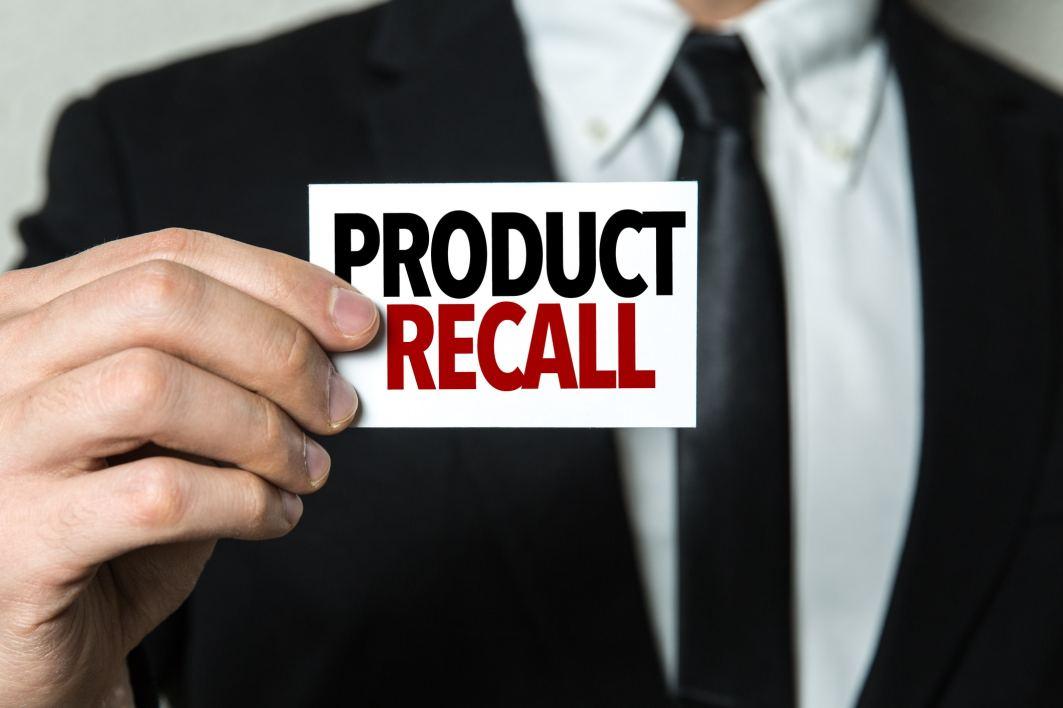 Businessman holding a card written: Product Recall