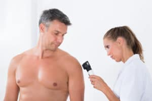 Female Doctor Examining Skin Of Male Patient With Possible Skin Cancer