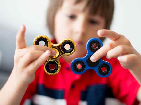 Young boy playing with a fidget spinner