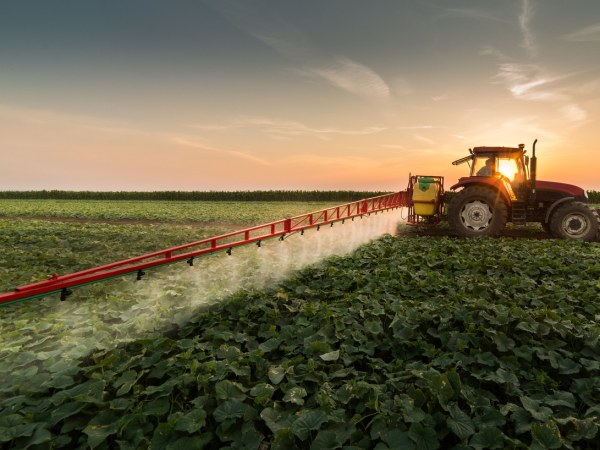 Tractor spraying paraquat on a field
