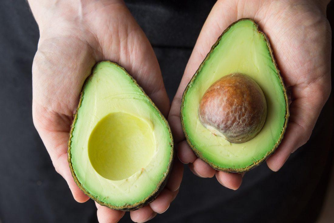 Hands holding a ripe California grown avocado.