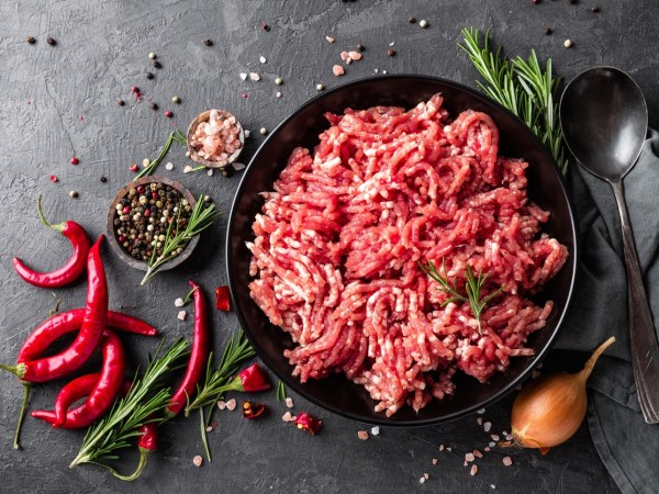 Image of raw ground beef in pan with red and green peppers on the side