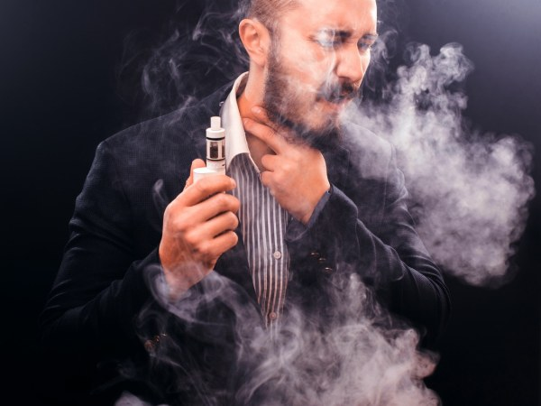 Man in button-up shirt and blazer appearing to cough while holding vape device in his hand