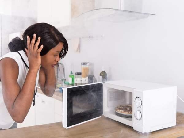 woman with microwave door open, hands on head in shock