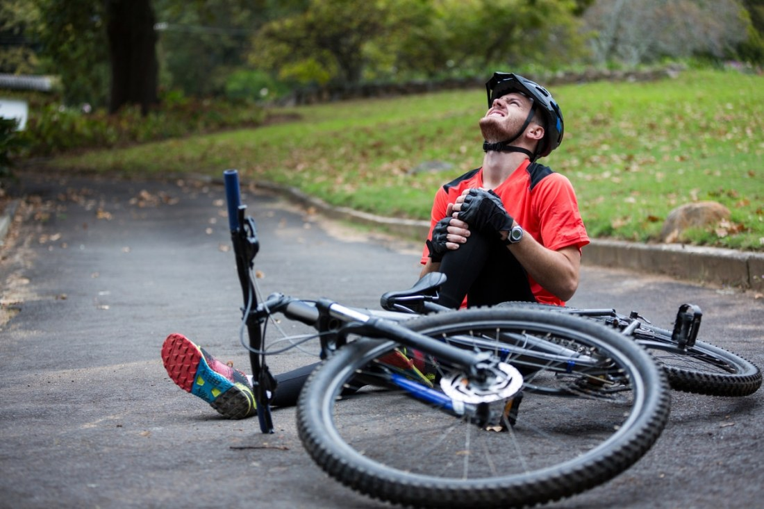 image of man who has fallen off a bike and has injured his knee