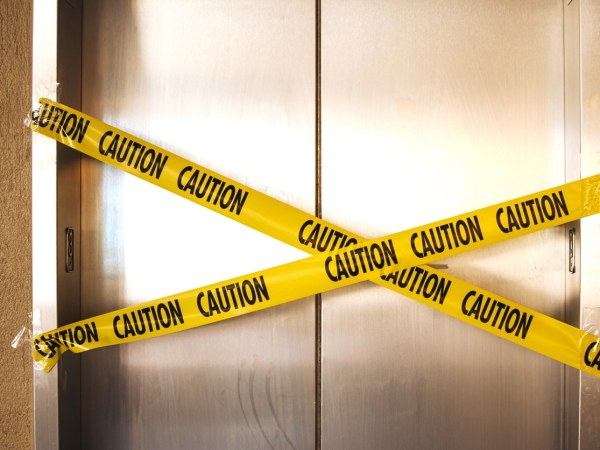 elevator doors with caution tape across them in an X configuration