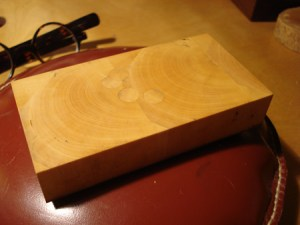 A prepared and repaired boxwood block sitting on an engraver's pillow ready to be engraved.