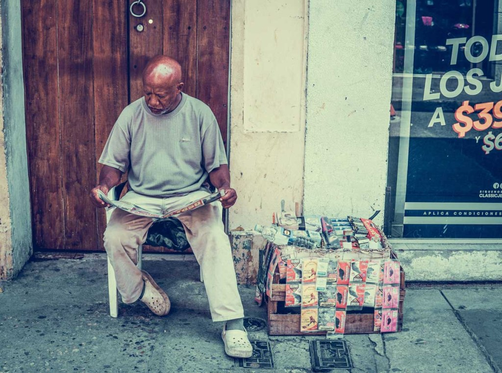 Homem a vender jornais na rua na Colômbia