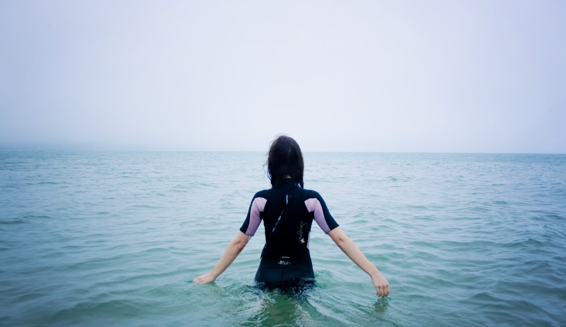 Teen girl wading into sea wearing wetsuit