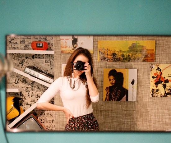 Girl's reflection in front of wide rectangle mirror. Retro style hotel in Rome Italy.