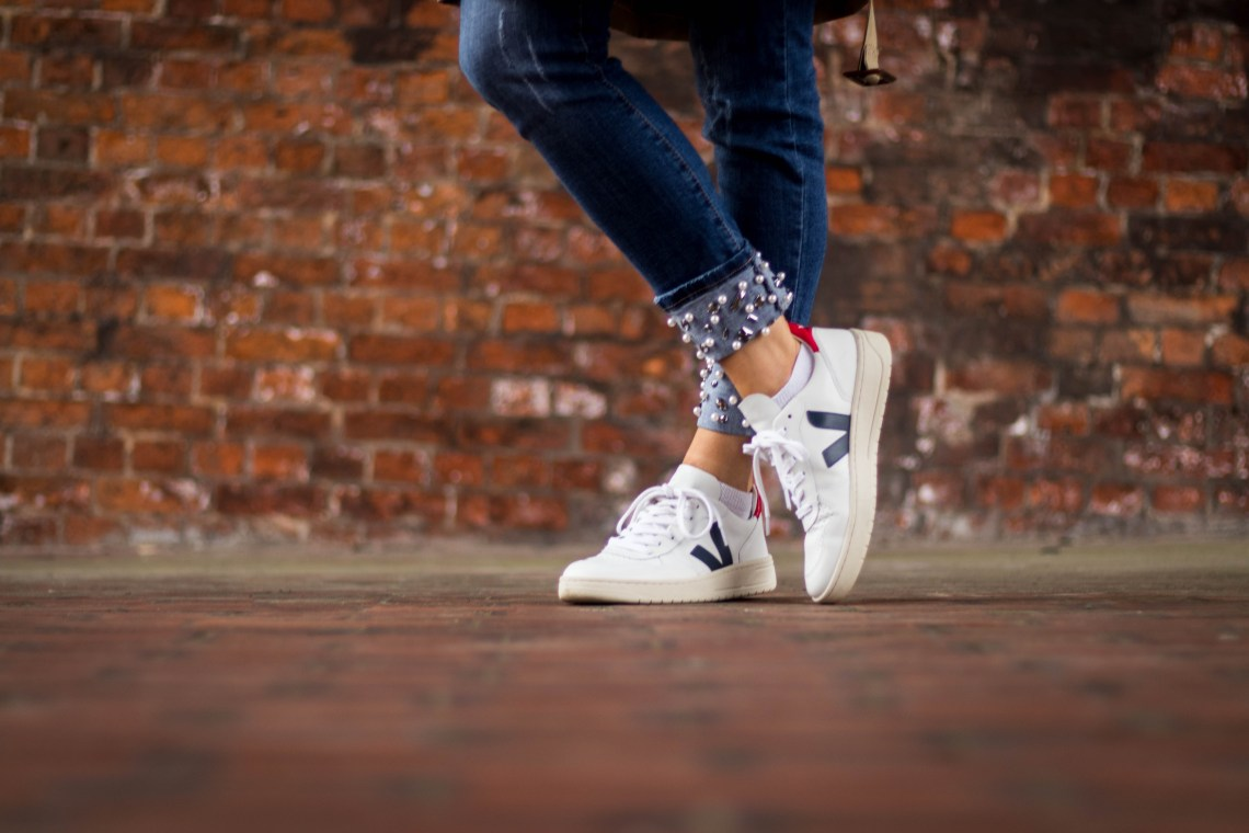 Blue jeans and Veja white trainers in front of wall