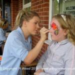 Katrina applying twirls to a face paint design