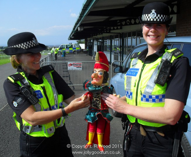 Mr Punch held by two female police officers.
